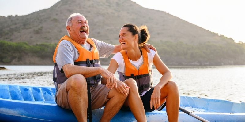 man and woman sitting on kayak laughing