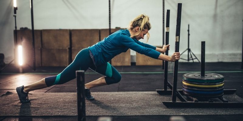 woman pushing weighted sled