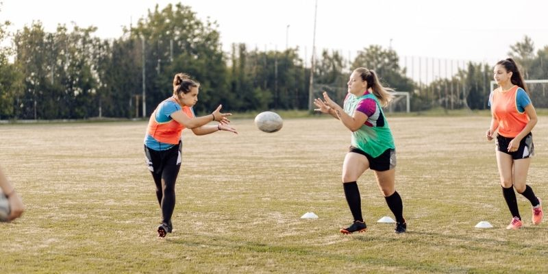 girls passing rugby ball